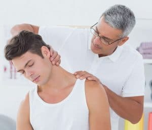 chiropractor examining a male patients neck