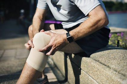 man holding his knee due to knee pain