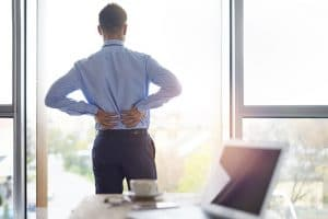 young business man holding his lower back due to pain