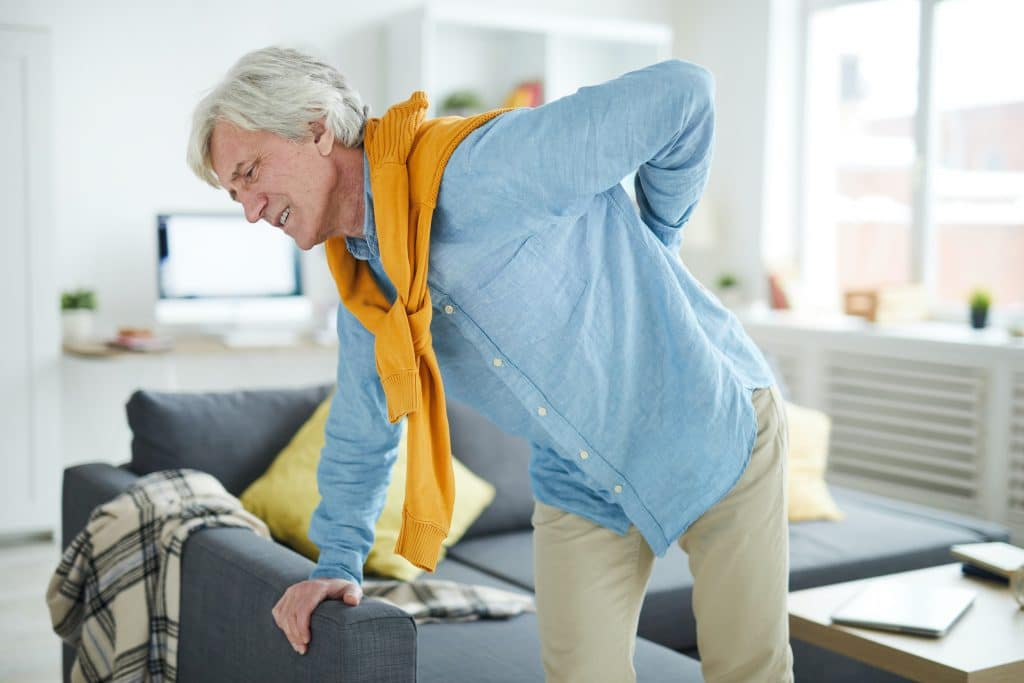 elderly man having back pain getting out of the chair