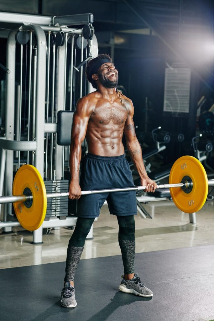 Young male deadlifting heavy weight at the gym