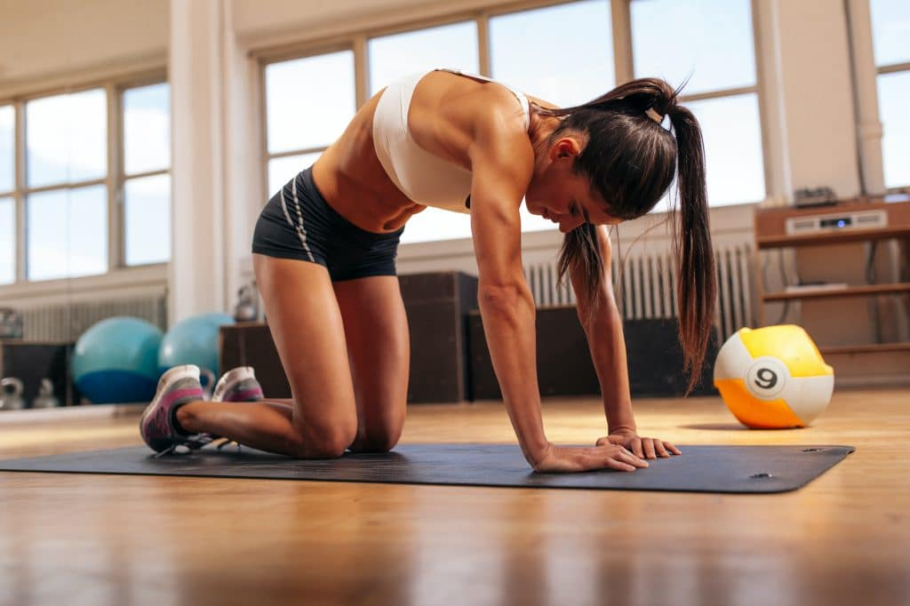 young woman performing cat camel lower back mobility exercise