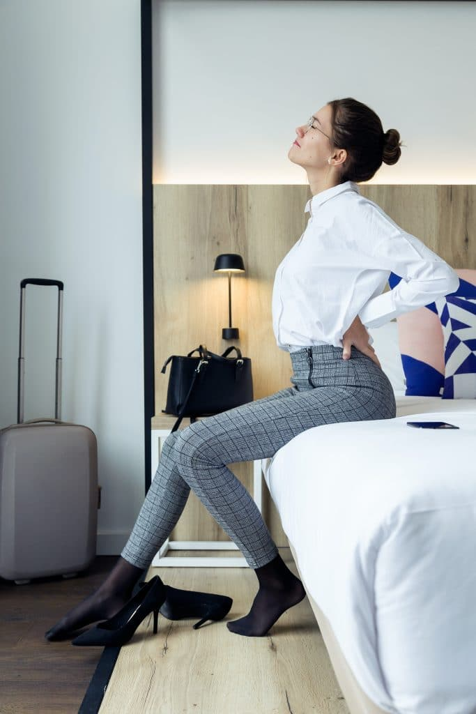 young woman sitting on the edge of her bed having back pain