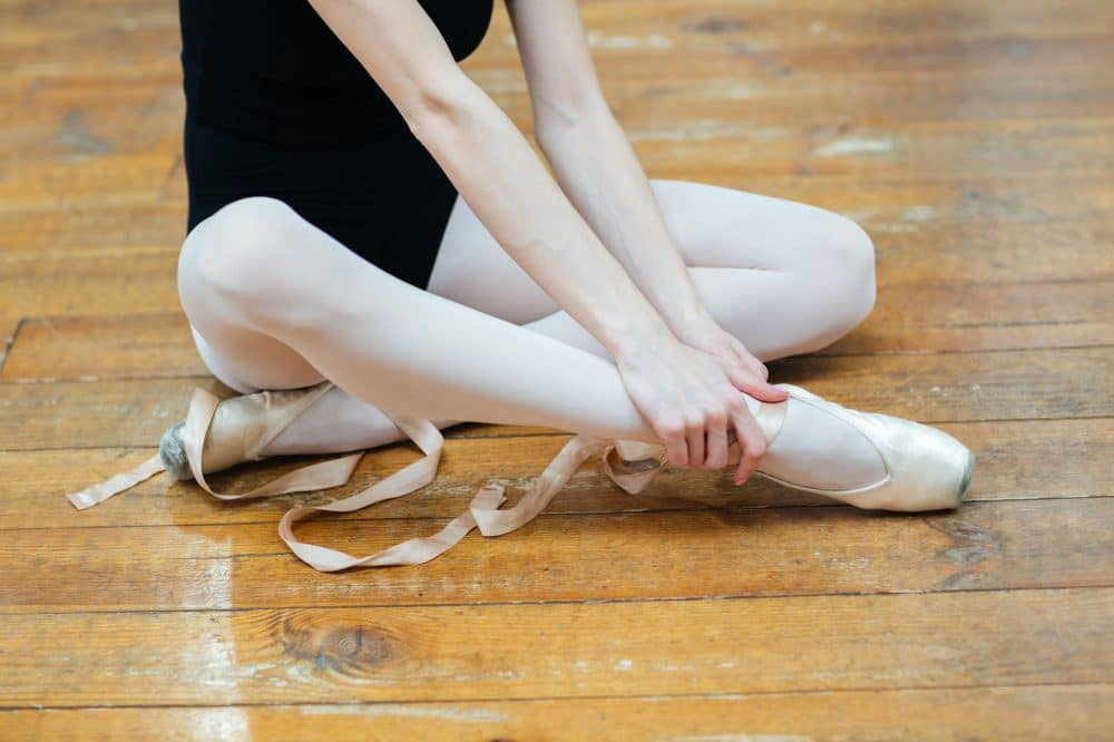 dancer holding her ankle due to an injury