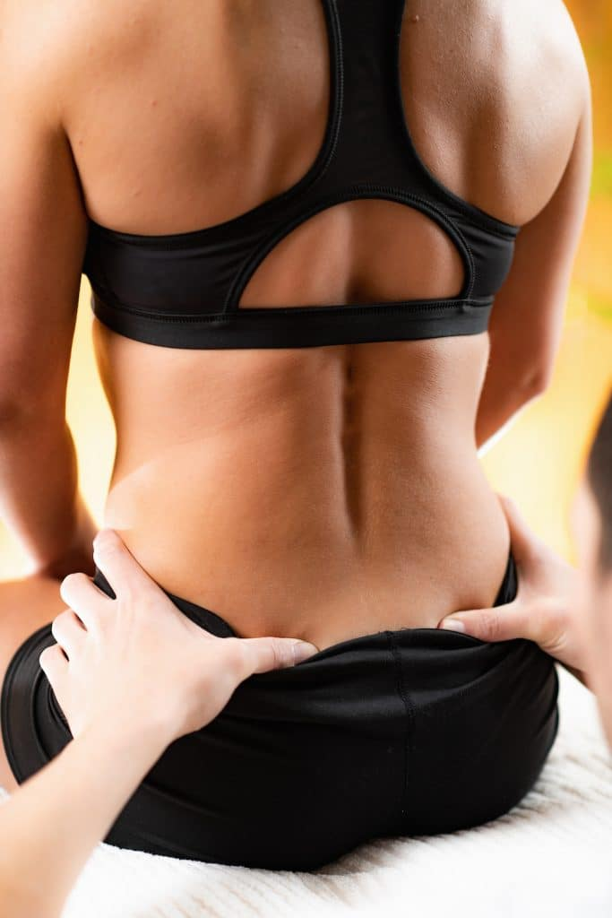 young female having her back examined by a chiropractor