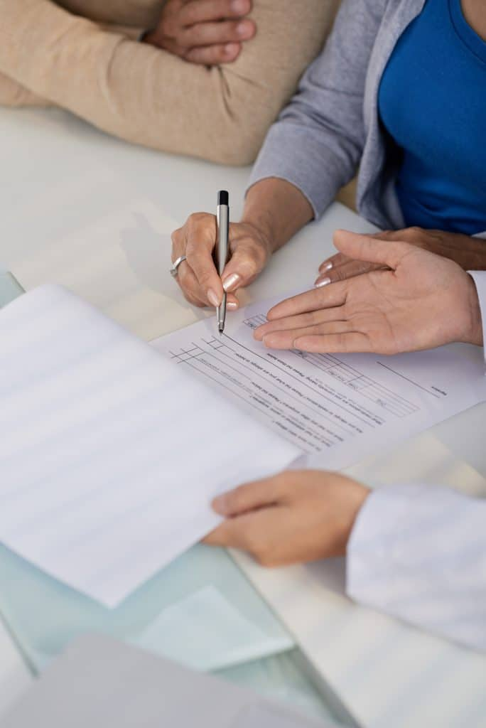 doctor asking patients to sign paperwork