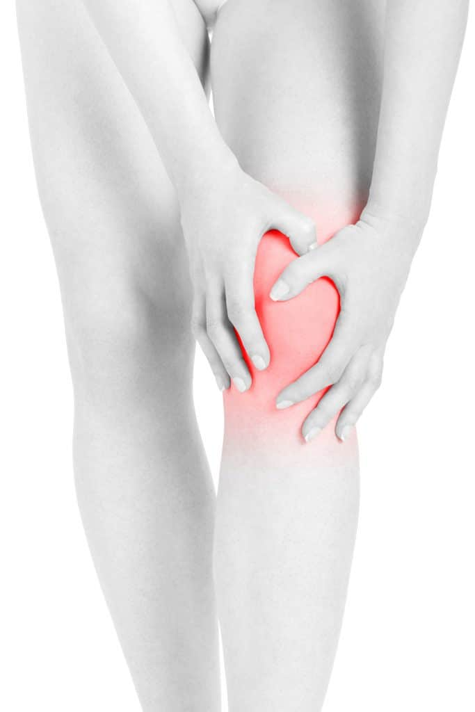 young female holding her knee due to inflammation