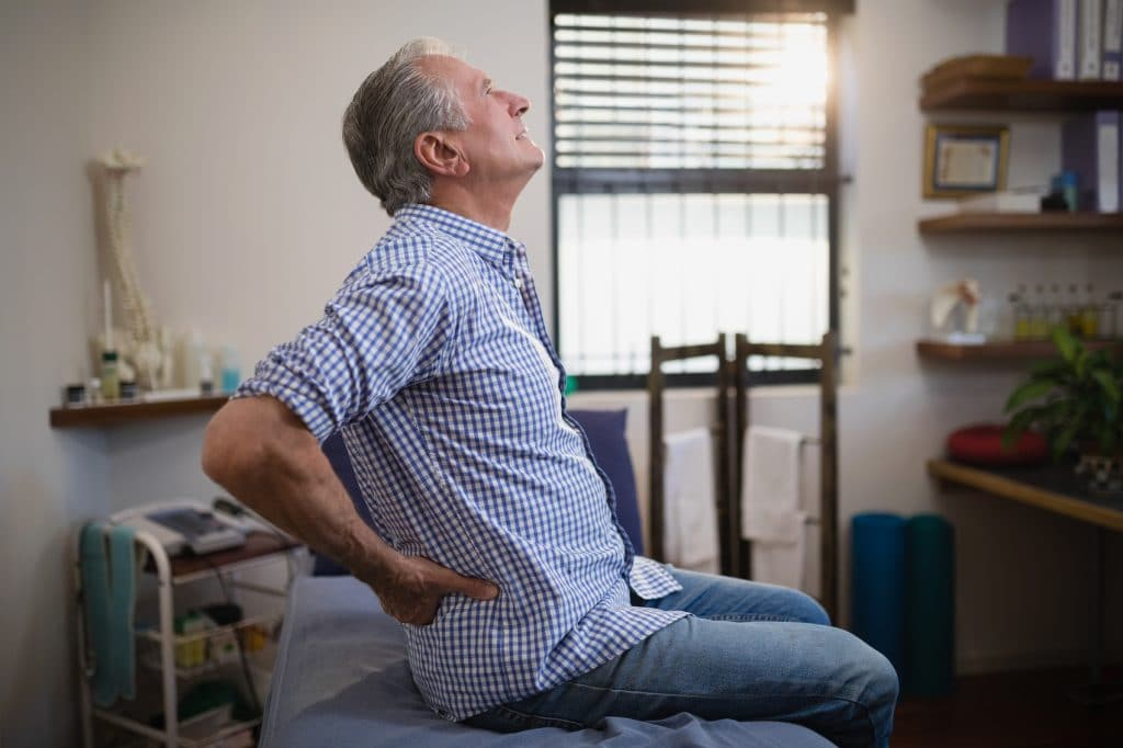 Elderly man holding his lower back and hips due to pain