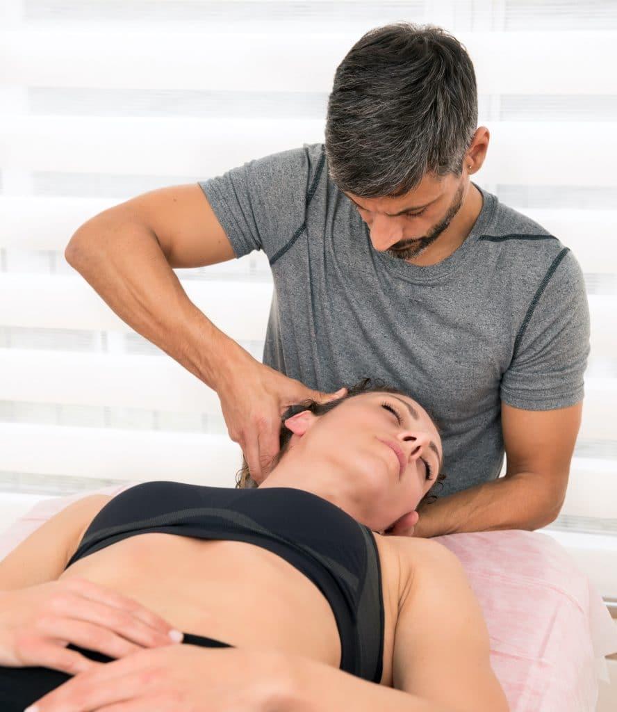 chiropractor adjusting female patient neck