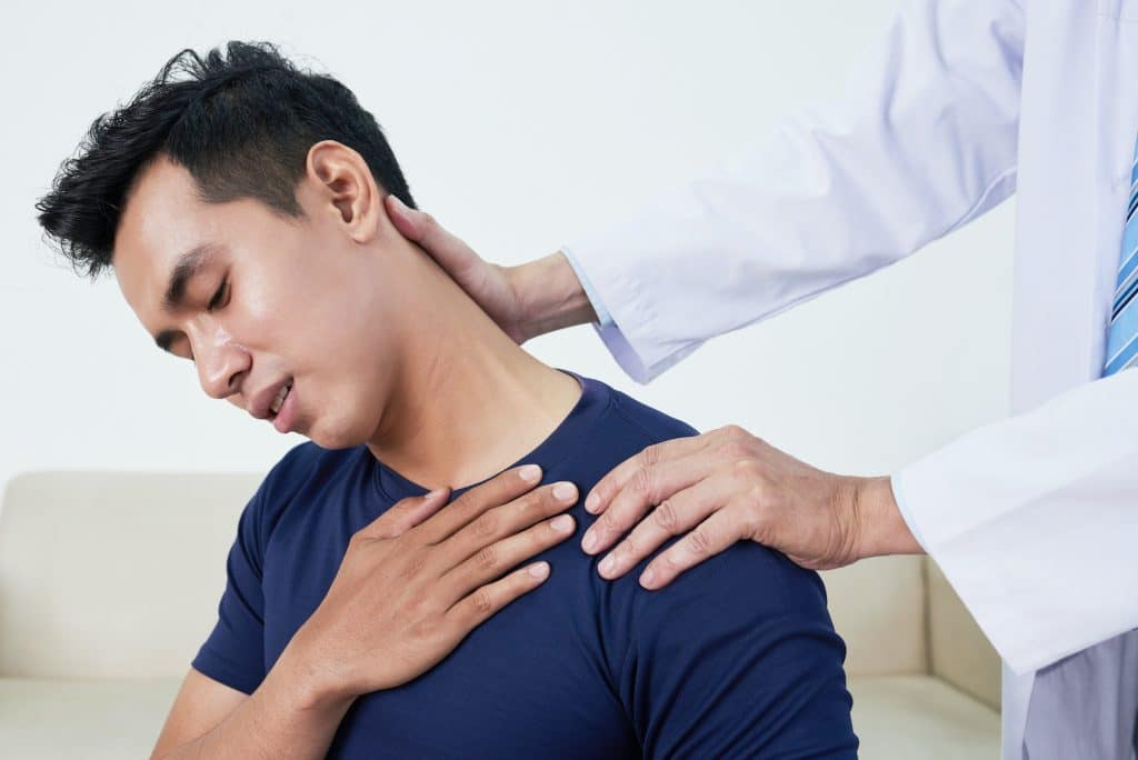male patients neck being examined by a doctor