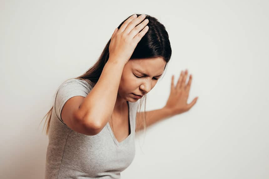 Woman holding her head while leaning on the wall trying to keep her balance due to vertigo.