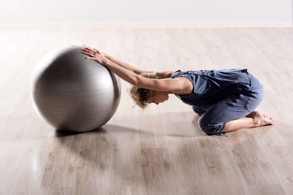 Woman doing stretching exercises with a balance ball.